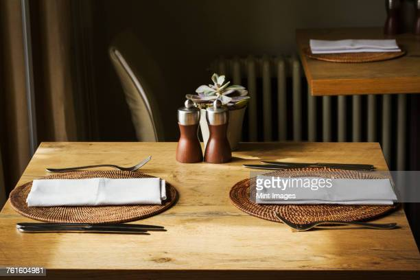 Wooden table set with place mats, napkins and cutlery in a restaurant.