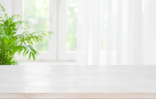 Wooden table top on blurred background of half curtained window 1126636035