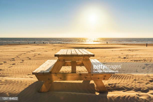 wooden table with benches on the beach - picnic table stock pictures, royalty-free photos & images