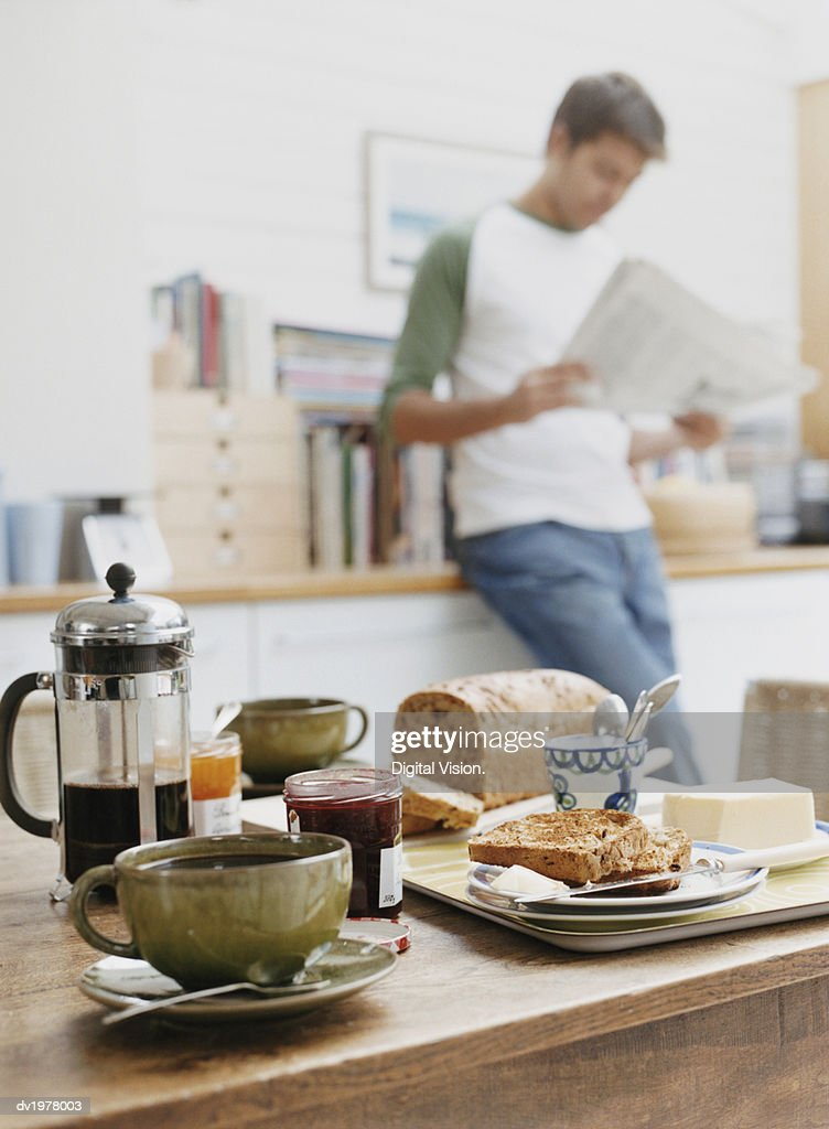 Wooden Table With Breakfast, Man Reading Newspaper in the Background : Stock Photo