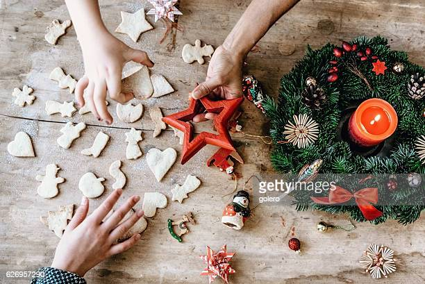 wooden table with hands holding cookies and christmas decoration