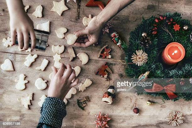 wooden table with hands preparing cookies and christmas decoration