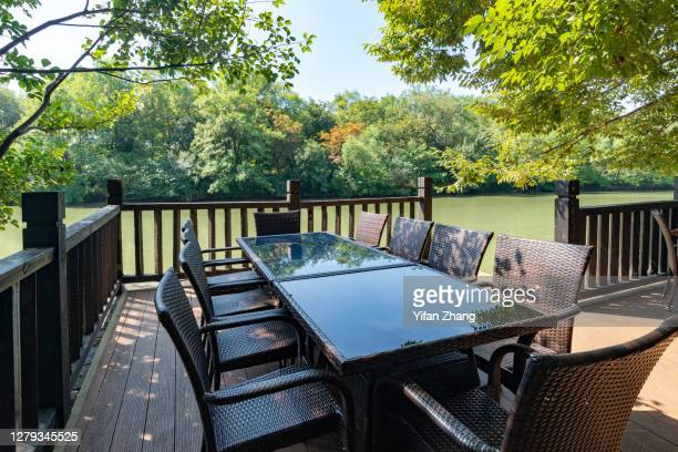 a wooden table with multiple chairs in a corner of public park - changzhou stock pictures, royalty-free photos & images