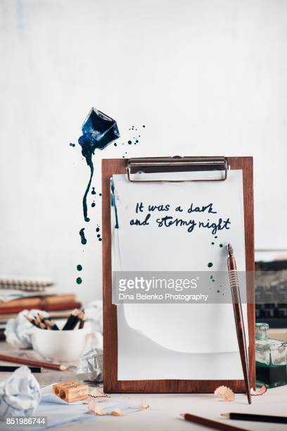 Wooden tablet with blank pages and flying inkwell. Dynamic still life with spilled ink. Creative writing concept. Overcoming creative block and searching for new ideas.