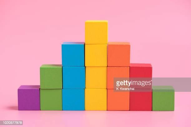 wooden toy blocks against pink background - pilha arranjo imagens e fotografias de stock