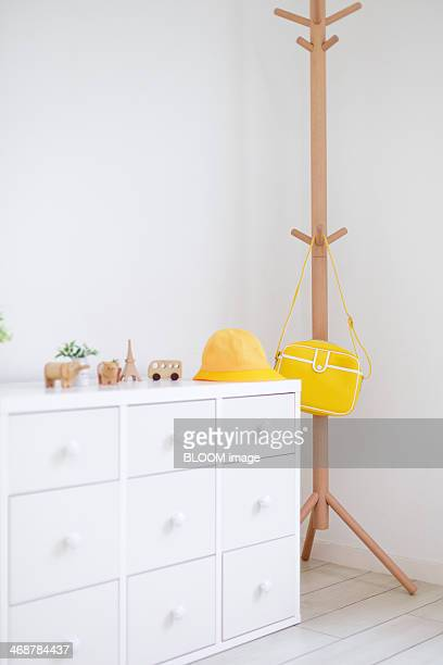 Wooden toys on chest of drawers and coat hanger in white room