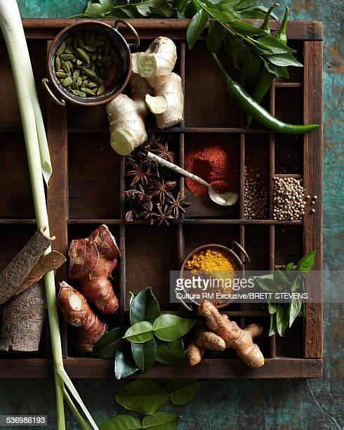 Wooden tray with compartments filled with raw herbs and spices