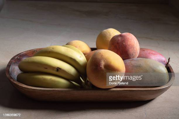wooden tray with fresh fruit: bananas, peaches, mango - dorte fjalland stock pictures, royalty-free photos & images