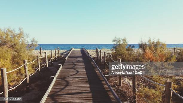 Wooden Walkway By Sea Against Clear Sky