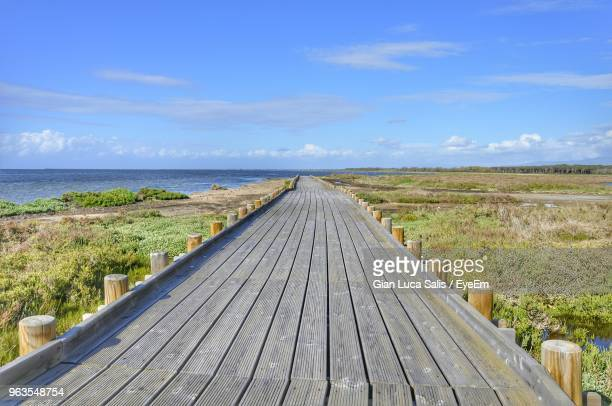 wooden walkway by sea against sky - parallel stock photos and pictures