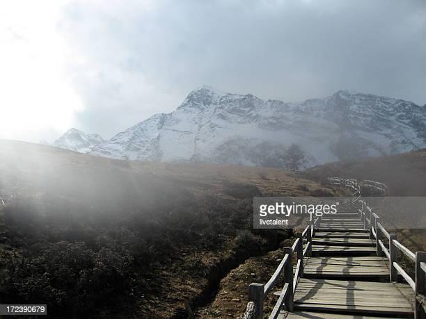 Hölzerner Fußweg im Nebel führt zu den Jade Dragon Snow Mountain