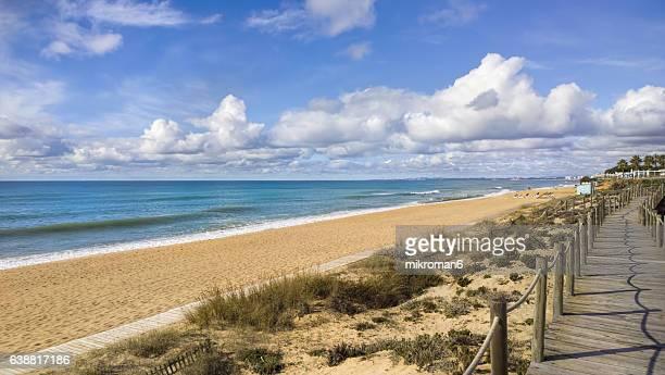 wooden walkway to the beach praia do garrão poente (dunas douradas). faro. portugal - faro city portugal stock photos and pictures