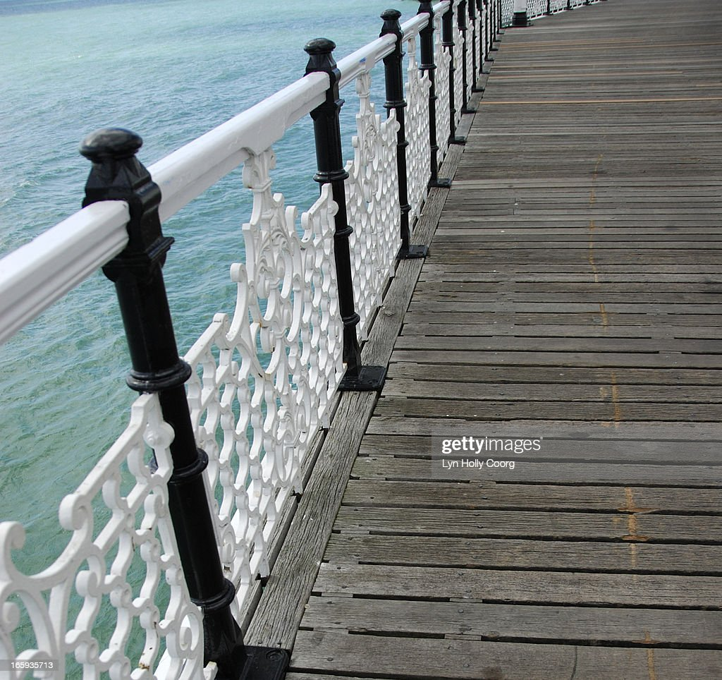 Wooden walkway with wrought iron railings : Stock Photo