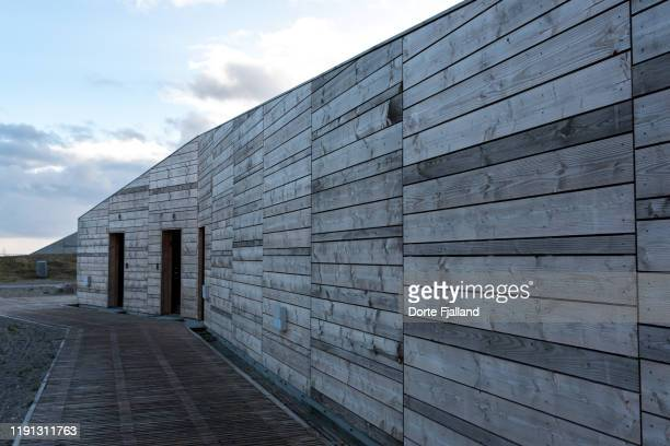 wooden wall of a building with some open doors and a blue sky above - dorte fjalland stock pictures, royalty-free photos & images