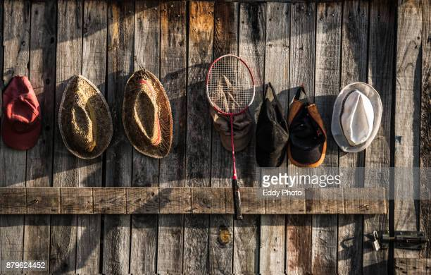 Wooden wall with different hanging hats and a tennis racket