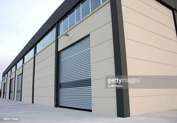 a wooden warehouse building lit up by the sun - industrial door stock pictures, royalty-free photos & images