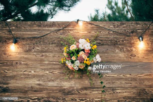 wooden wedding backdrop with light garland and flower arrangement - wedding background stock pictures, royalty-free photos & images