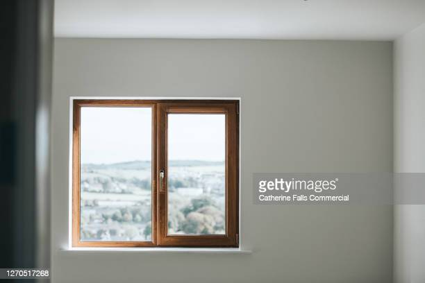 wooden window frame set in a plain white wall in an empty room - window stock pictures, royalty-free photos & images