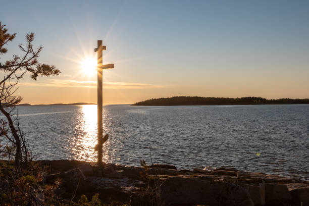 Wooden worship cross on the shore of a deserted lake in the sunbeams of the sunset