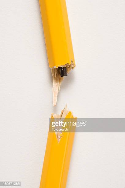 Wooden yellow pencil broken with lead exposed against white background