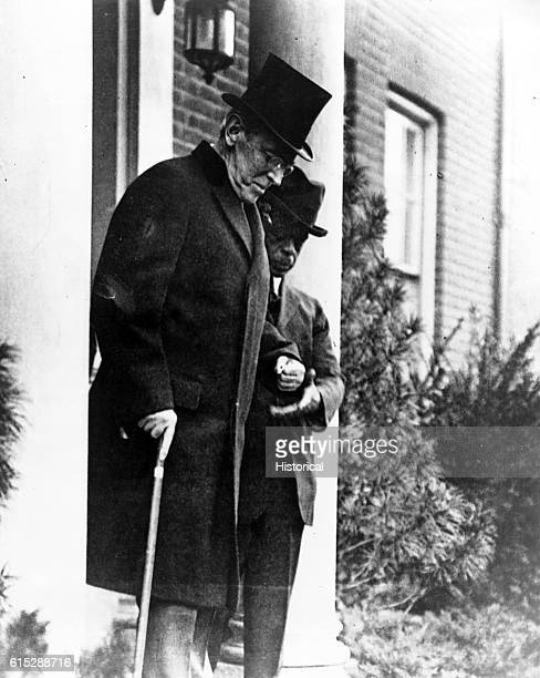 Woodrow Wislon , the twenty-eighth President of the US, walks down the front steps at his home. He wears a top hat.