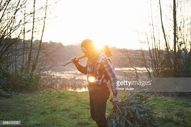 Woodsman with axe over his shoulder in forest at sunset