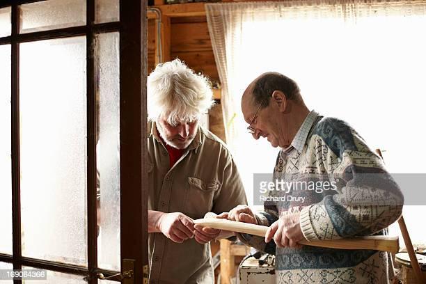 Woodsmen examining new adze handle in workshop
