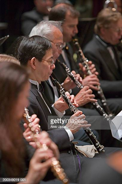 woodwind players in orchestra during performance (focus on oboes) - oboe stock-fotos und bilder