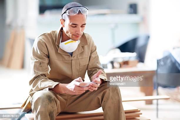 Woodwork, carpenter using mobile phone