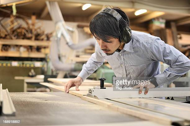 Woodworker cutting wooden plank