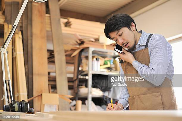 Woodworker is on the phone with smartphone