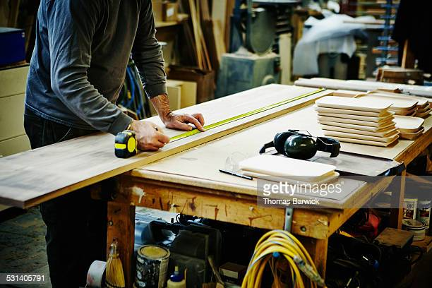 Woodworker measuring board in woodshop