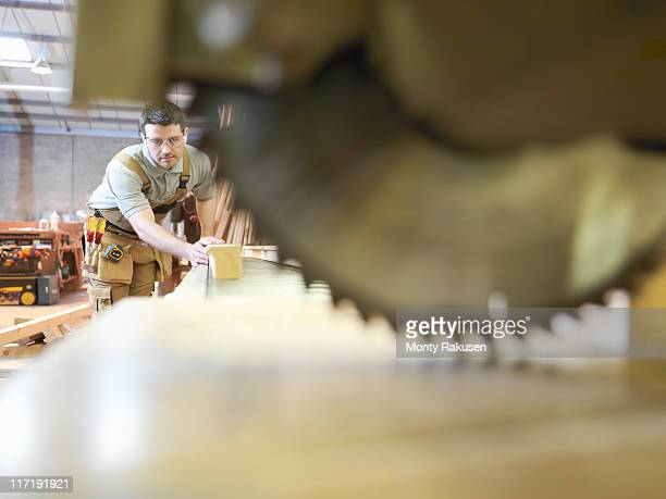 Woodworker sawing timber