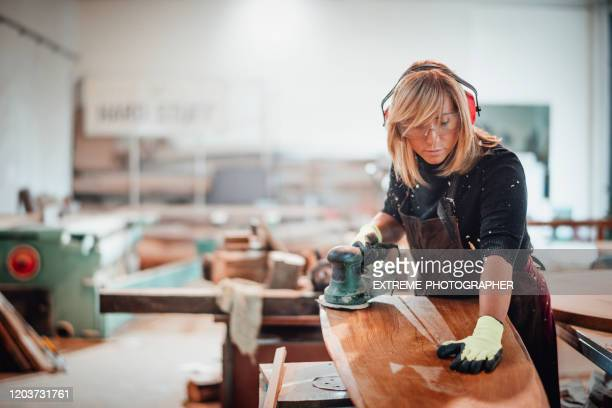 woodworker using a hand sander to sand down a wooden surface - craftsperson stock pictures, royalty-free photos & images