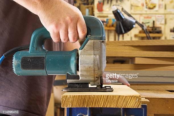 Woodworker mit einer elektrischen Stichsäge