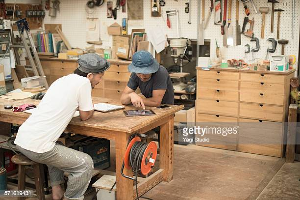 Woodworker using digital tablet in workshop