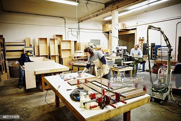 Woodworkers working in custom cabinet workshop