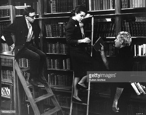 Woody Allen and Paula Prentiss work on library ladders in a scene of the movie What's New Pussycat circa 1965