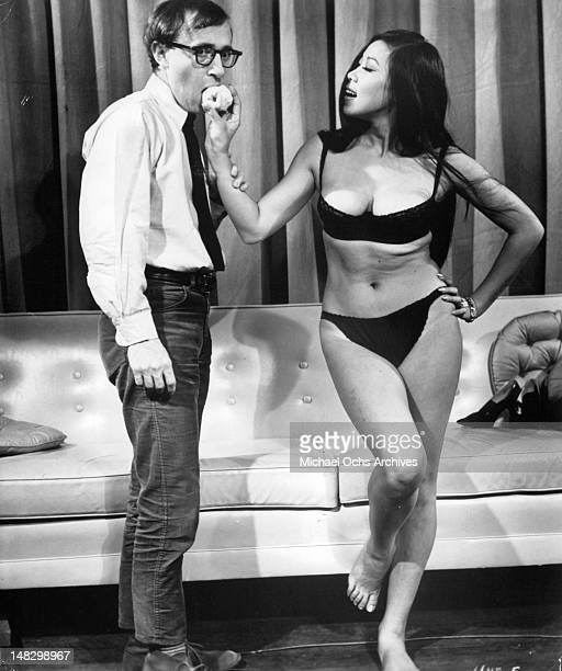 Woody Allen getting apple from Akiko Wakabayashi in a scene from the film 'What's Up Tiger Lily' 1966