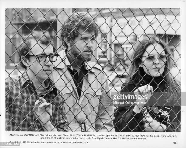 Woody Allen Tony Roberts and Diane Keaton standing behind a chain link fence in a scene from the film 'Annie Hall' 1977