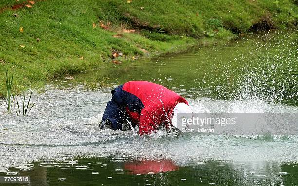 Woody Austin of the U.S. Team falls in the water after hitting a shot from the water on the 14th hole during the round two fourball matches at the...