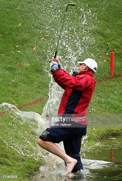 Woody Austin of the U.S. Team hits a shot from the water on the 14th hole during the round two fourball matches at the Presidents Cup at The Royal...