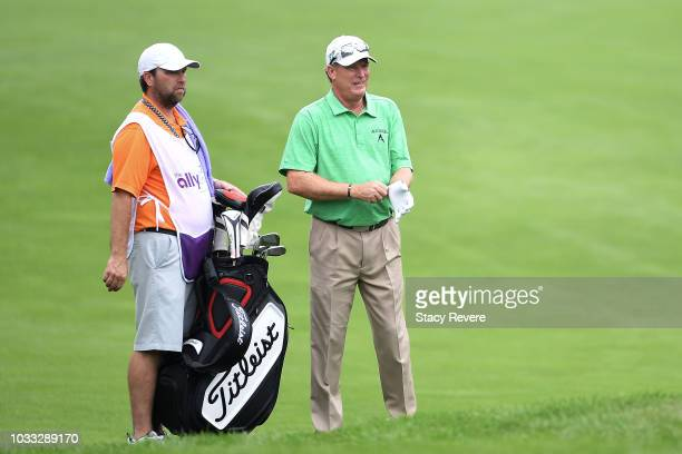 Woody Austin speaks with his caddie on the first hole during the first round of the Ally Challenge presented by McLaren at Warwick Hills Golf Country...