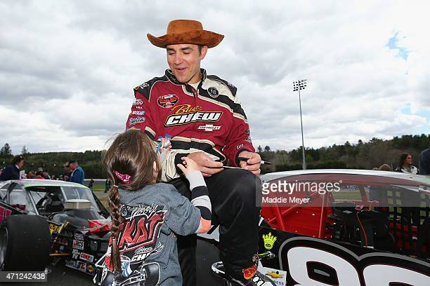 Woody Pitkat driver of the Buzz Chew Chevrolet/Elbow East Chevrolet talks with his daughter during the NAPA Auto Parts Pit Party before the start of...