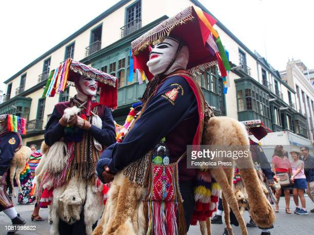 Wool masked men with a llama taxidermy participating of Quechuaspeaking Indigenous people devotees of San Sebastian carry on a religious procession...