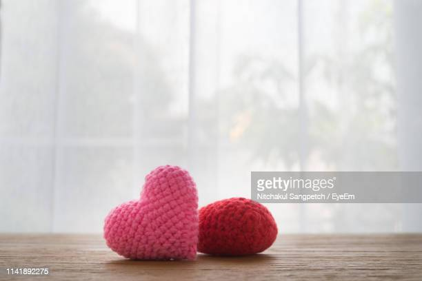 woolen heart shape on table against window - wool stock pictures, royalty-free photos & images