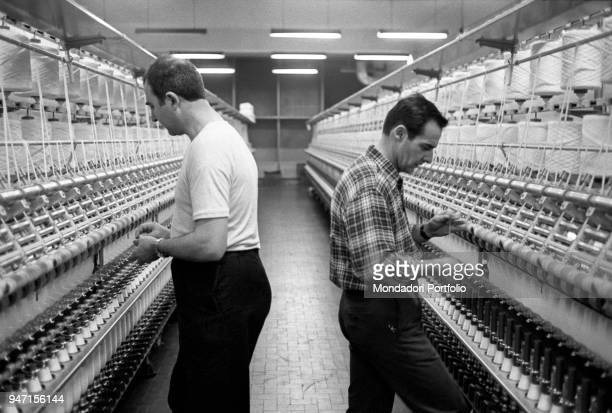 Woolen mill workers working in front of a spinning machine in the district of Biella Italy 1968