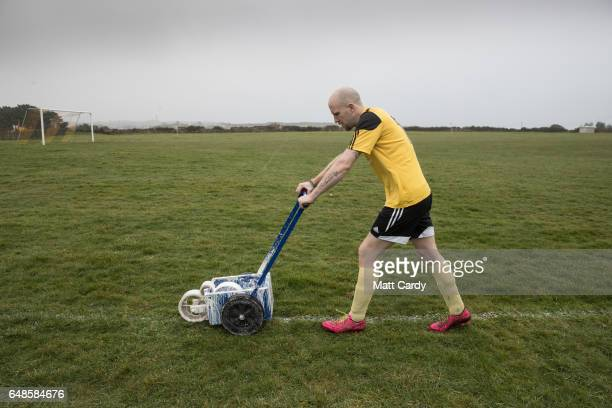 Woolpack Wanderers player Anthony Gibbons paints the white line on the football pitch at the Garrison soccer field on St Mary's on the Isles of...