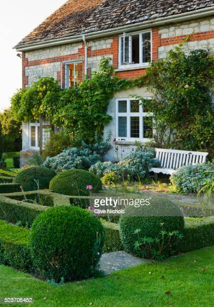 Woolstone Mill house, Oxfordshire: The house with Formal Parterre, Box Balls and Bench.