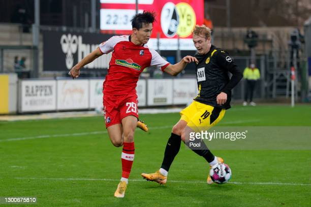 Wooyeong Jeong of Sport-Club Freiburg is challenged by Julian Brandt of Borussia Dortmund during the Bundesliga match between Sport-Club Freiburg and...